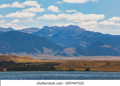 Summer day at Ennis Lake in central Montana, USA. Steep mountain cliffs in distance.