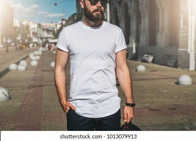 Summer day. Front view. Young bearded millennial man dressed in white t-shirt and sunglasses is stands on city street. Mock up. Space for logo, text, image. Instagram filter, film effect, bokeh effect