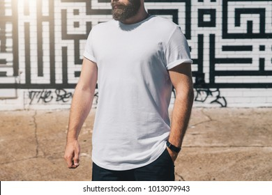 Summer day. Front view. Young bearded millennial man dressed in white t-shirt is stands against brick wall. Mock up. Space for logo, text, image. Instagram filter, film effect, bokeh effect.