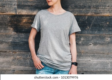 Summer day. Front view. Young millennial woman dressed in gray t-shirt is stands against gray wood wall. Mock up. Space for logo, text, image.