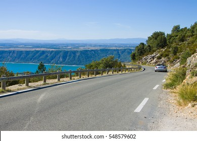 Summer day landscape with road and car trip way. Road D71 alone Verdon river canyon, view on Saint Croix lake and plateau behind. France, Provence.
