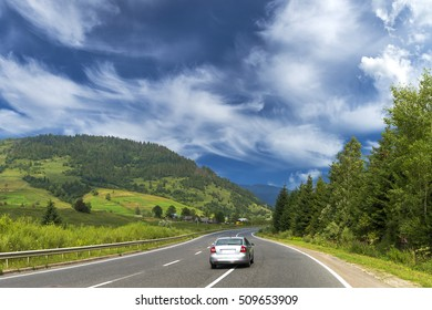 summer day landscape with road cloudy sky and car trip way