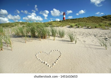 summer day at Lighthouse List East on the island Sylt with an heartr in the sand dunes