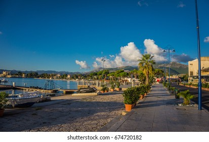 Summer day in Mondello (Palermo, Sicily) road with trees and dock view, Italy
