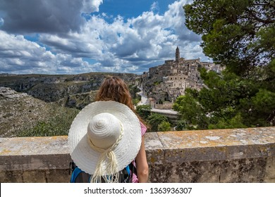 Summer day scenery street view of the amazing ancient town of the Sassi with white puffy clouds moving on Italian blue sky. Matera, Basilicata, Italy. Young woman tourist with white hat enjoys view
