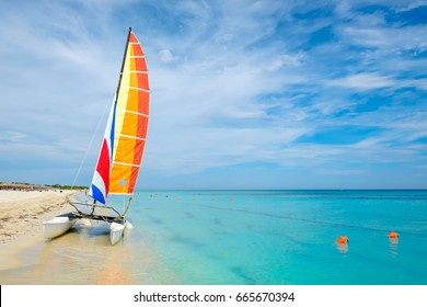 Summer day at Varadero beach in Cuba with a colorful sailboat