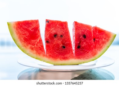 Summer day with vivid vibrant colorful red watermelon slice cut outside in Italy on white plate and glass table with seeded black seeds