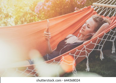Summer day, young woman lying in orange hammock in park and listening to music on smartphone.Girl blogging, chatting, shopping online, using digital gadget.Lifestyle. Instagram filter. Social network.