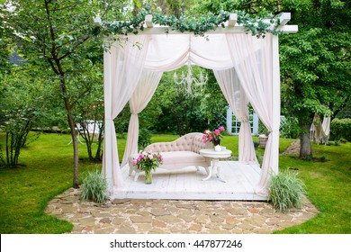 Summer delicate elegant gazebo in lush gardens.Exquisite classic sofa decorated with flowers in a gazebo with white curtains in the fresh garden
