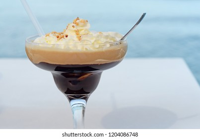summer dessert with dark iced coffee an soft whipped cream, topped with hazelnut crunch