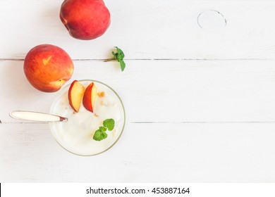 Summer dessert with peaches on wooden white background. Peach yogurt. Flat lay, top view