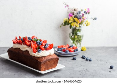 Summer dessert with strawberries and blueberries.  Cake loaf with buttercream icing and topped with fresh ripe summer colorful fruits and berries, selective focus, close up