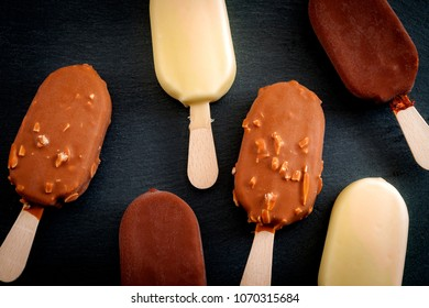 Summer desserts and cold snacks concept with many many lollies or ice cream bars on a stick in assorted flavors -  white chocolate, hazelnut and classica - on a dark black stone background