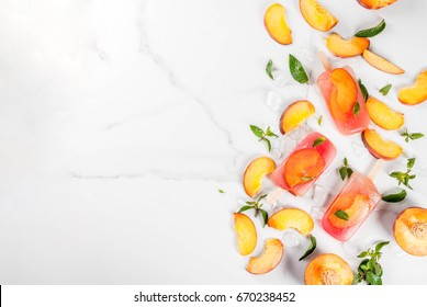 Summer desserts. Frozen drinks. Sweet fruit popsicles from frozen peach tea with mint. On a white marble table, with ingredients - peaches, mint, ice. Copy space top view