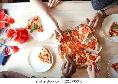 Summer dinner or lunch at street cafe indoor. Flat-lay of people hands taking freshly baked Italian pepperoni pizza with salami slices over white wooden table, top view.
