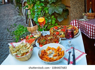 A summer  dinner .Unidentified people eating traditional italian food in outdoor restaurant in Trastevere district in Rome, Italy.   .Tasty and authentic Italian kitchen