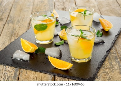Summer drink. Citrus lemonade with mint and ice on white wooden background.