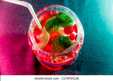 Summer drink coctail in glass jar, berries and mint on wooden table