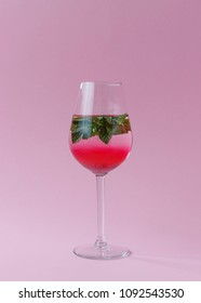 Summer drink with diffusing grenadine syrup, fresh mint leaves in a wineglass standing on a pastel pink background.