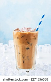 Summer drink ice coffee with cream in a tall glass with straw surrounded by ice on white marble table over blue background. Selective focus, copy space for text.