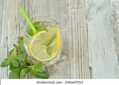 summer drink on a wooden table with mint and citrus