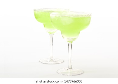 Summer drinking, fancy beverages and party cocktails concept theme with two frozen margaritas in clear glasses isolated on white background