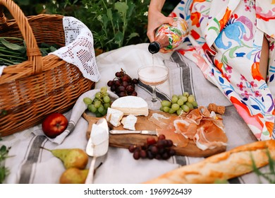 A summer eco picnic in the field with straw basket, flowers, wine, fruits, baguette, cheese Camembert