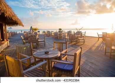 Summer empty open air restaraunt near sea at exotic island on beautiful sunset