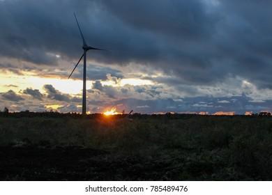 summer evening  against sunlight beautiful clouds and sky wind turbines generators sunset