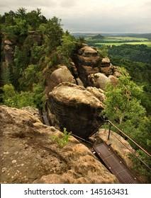 Summer evening before storm on peak path in Saxon Switzerland, grey sky over sandstone rocks.