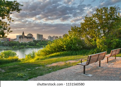 A summer evening with an empty bench along the South Saskatoon river looking to the west and the colorful sunset over the city.