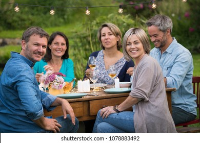 A summer evening of friends in their 40s gather around a table in the garden to share a meal and have fun together.