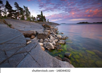 Summer evening landscape with sea coast and alga covered stones from Uutela nature park, Finland