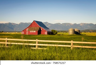 Summer evening with a red barn and silos in rural Montana with Rocky Mountains in the background.