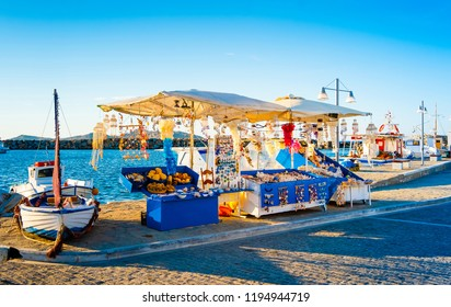 Summer evening view of souvenir booth at stony berth and turquoise bay of greek island Paros