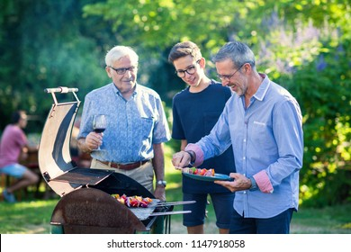 In summer, the family gathered for a barbecue in the garden. Three generations of men are in charge of grilling meat