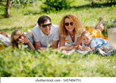 Summer family picnic on grass in gardens under shade of trees. Mother, father, two children lying on their bellies on white tablecloth next to their food. Laughing together, eating. In sunglasses
