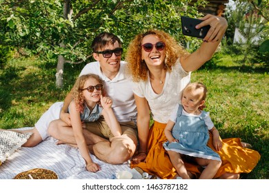 Summer family picnic on grass in gardens under gentle shade of trees. Mother, father, two children sitting on white tablecloth next to their food. Taking selfie, posing for photo. In sunglasses.