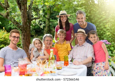 In summer, Family reunion around a picnic table in a beautiful garden. All generations pose for the camera. Shot with flare