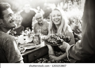 In the summer, a family of three generations gathered around a table in the garden to share a barbecue. close-up on a grilled meat dish presented to the guests. black and white