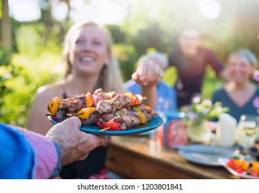 In the summer, a family of three generations gathered around a table in the garden to share a barbecue. close-up on a grilled meat dish presented to the guests