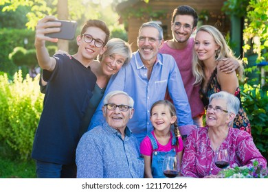 In the summer, a family of three generations gathered around a table in the garden to share a meal. A teenager child does a selfie with all the guests