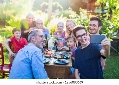 In the summer, a family of three generations gathered around a table in the garden sharing a meal. A teenager does a selfie with all the guests