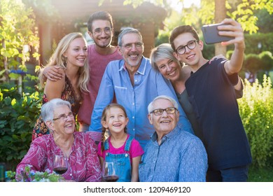 In the summer, a family of three generations having fun around a table in the garden sharing a meal. A teenager child does a selfie with all the guests