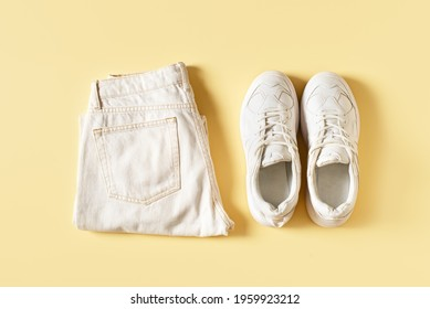 Summer fashio set with white sneakers and jeans pants, top view, flat lay on yellow backgrpund