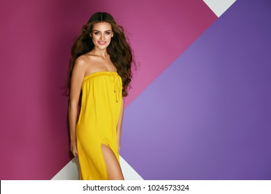 Summer Fashion. Beautiful Woman In Dress On Colorful Background. Gorgeous Sexy Girl In Fashionable Trendy Yellow Clothes With Hair Style And Beauty Makeup On Bright Purple Background. High Resolution.