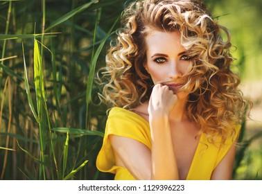 Summer fashion close up portrait of stunning blonde woman on the beach. Wearing long yellow dress. Perfect make up and curls. Beauty portrait. Romantic mood. Enjoying sunlights. Sensual. Summer times