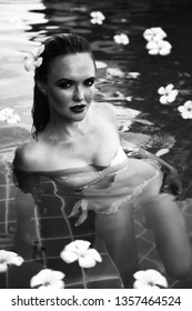 Summer fashion close up portrait of stunning ginger hair woman with freckles. Posing in the pool. With flower of plumeria in her hairs. Wearing white bikini. Glossy makeup, smoky eyes and wet hair.