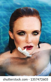 Summer fashion close up portrait of stunning ginger hair woman with freckles. Posing in the pool. With flower of plumeria in her lips. Wearing white bikini. Glossy makeup, smoky eyes and wet hair.