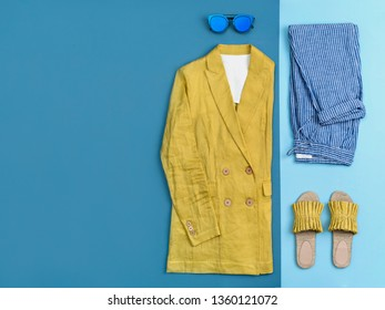 Summer fashion clothing and accessories flat lay. Urban female outfit on two-colored background: arranged on the right side yellow linen jacket, striped blue pants, blue sunglasses and yellow sandals.